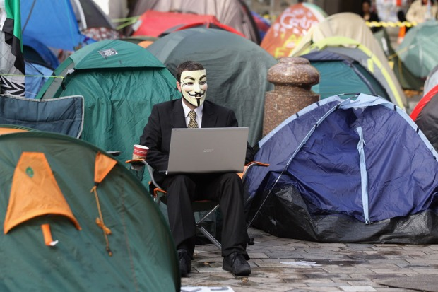 A mask-wearing protester uses his laptop computer in the Occupy LSX camp outside St Paul's Cathedral, ahead of a demonstration against higher tuition fees and privatization in universities on November 9, 2011 in London, England. Around 4,000 police officers were on duty and were allowed to deploy baton rounds if needed. (Oli Scarff/Getty Images) #
