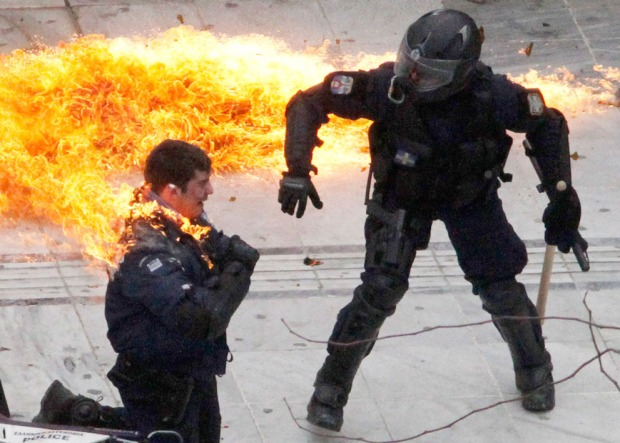 A motorcycle policeman is engulfed in flames as his colleague tries to help him after protesters threw a petrol bomb in Athens, Greece, on February 23, 2011. Scores of youths hurled rocks and petrol bombs at riot police after clashes broke out during a mass rally taking place as part of a general strike. (AP Photo/Dimitri Messinis)