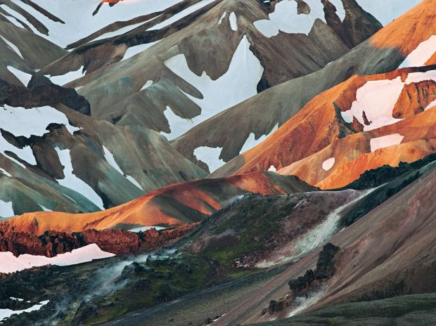The first beams of a June day spotlight a ridge of rusty volcanic rhyolite at Landmannalaugar, a hikers' favorite.